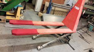 Höglyftande palltruck, bredda stödben och förlängning av gafflar.