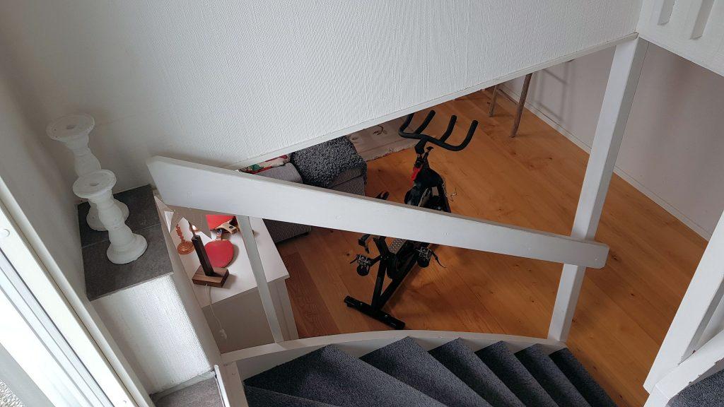 Rostfritt trappräcke med glas sektioner och handledare.