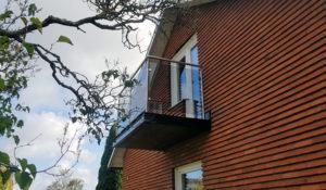 Rostfritt balkongräcke med rökfärgat glas.